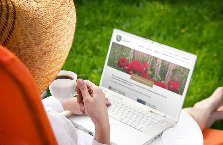 A lady looking at the Worshipful Company of Gardeners website on a laptop in the garden - mobile