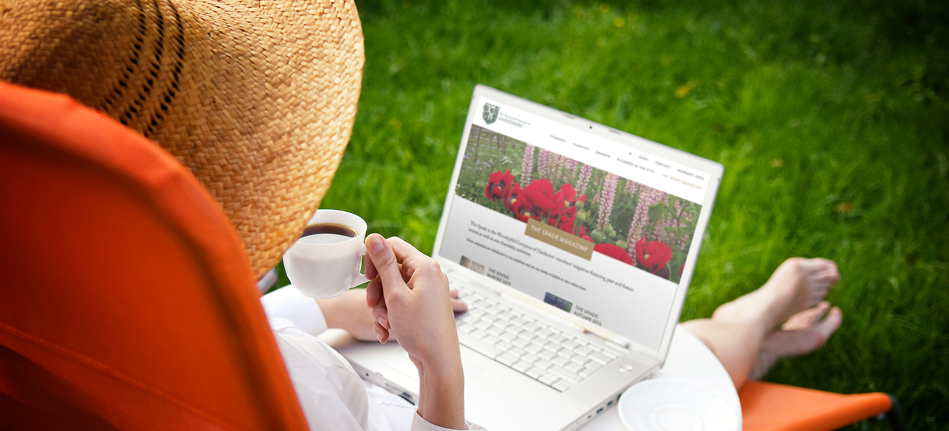 A lady looking at the Worshipful Company of Gardeners website on a laptop in the garden - desktop